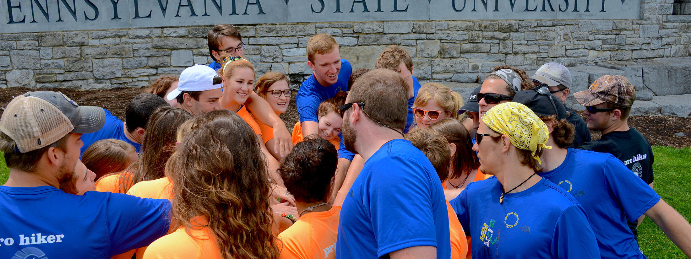 Students with hands in a circle next to The Pennsylvania State University sign